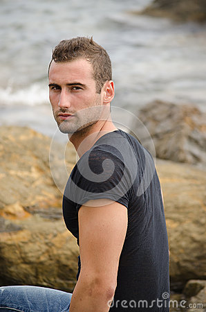 Handsome male model sitting on rock by the sea
