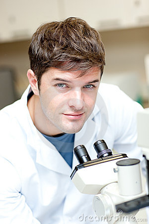 Handsome male scientist using a microscope