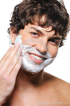 Handsome man applying shaving cream upon his face