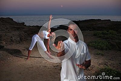 Handsome man on the beach meditating