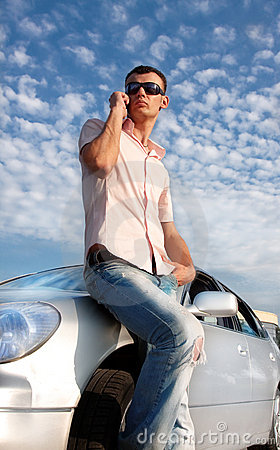 Handsome man calling by cellular phone near car