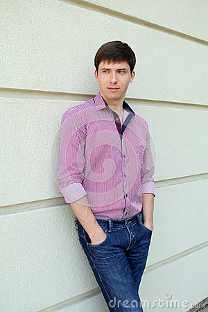 Handsome man casually leaning against the wall