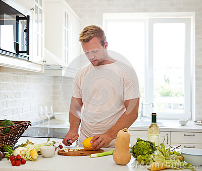 Handsome Man Cooking At Home Preparing Salad In Kitchen ...
