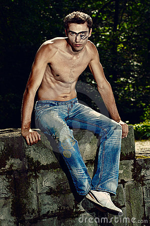 Handsome man in jeans trousers sitting on the wall
