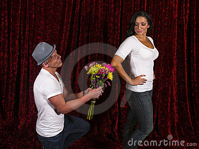 Handsome man kneels with flowers for girlfriend