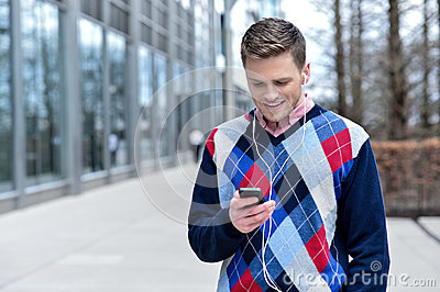Handsome man listening to music at outdoors