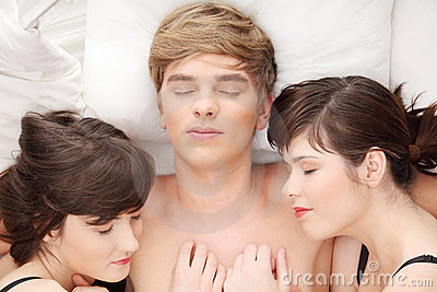 Handsome man lying in bed with two girls