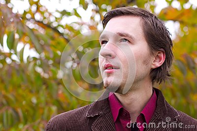 Handsome man portrait in autumn leaves background
