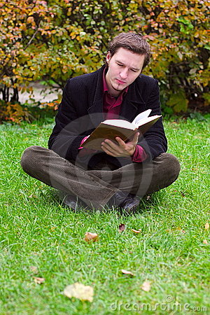 Handsome man reading book on a grass in autumn