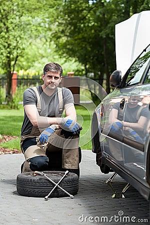 Handsome man repairing car outdoors