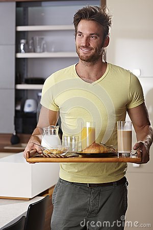 Handsome man serving breakfast for two