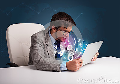 Handsome man sitting at desk and typing on laptop with 3d number