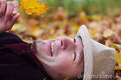 Handsome man smiling and lying in autumn leaves