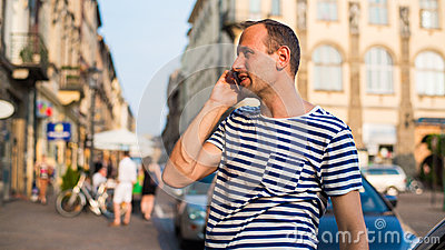 Handsome man speaking on the phone on city background.