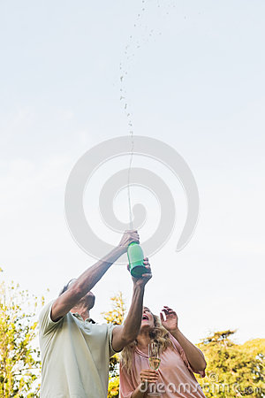 Handsome man spraying bottle of champagne with blonde partner