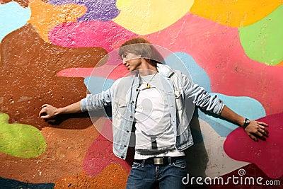 Handsome man standing near graffiti wall