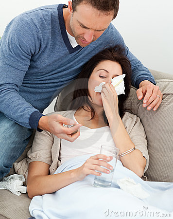 Handsome man taking care of his sick girlfriend