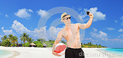 Handsome man taking a selfie on a tropical beach