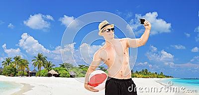 Handsome man taking a selfie on a tropical beach