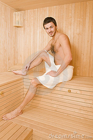 Handsome man in a towel relaxing in sauna