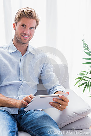 Handsome man using a tablet pc on his couch