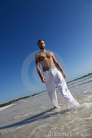 Handsome man walking in sea