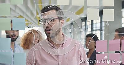 Handsome maschio leader spiega ai colleghi la nuova strategia del progetto durante l'incontro Uomo d'affari in 30 anni con il vet archivi video