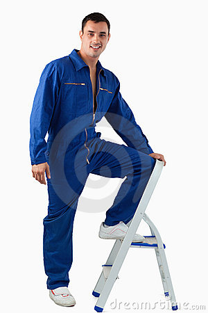A handsome mechanic climbing on a stool