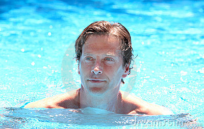 Handsome middle aged man swimming in outdoor pool