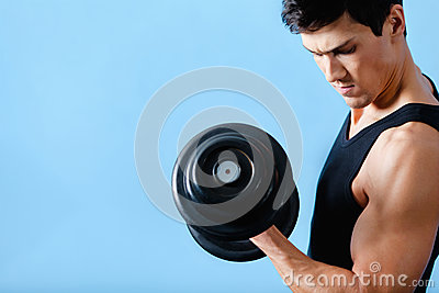 Handsome muscular man uses his dumbbell