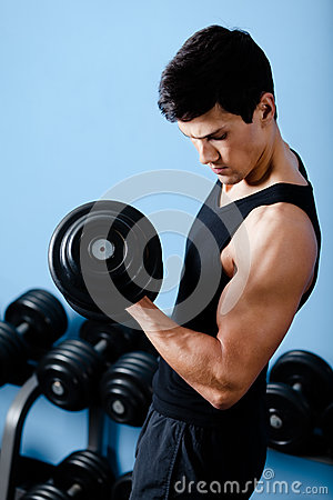 Handsome muscular sportsman uses his dumbbell