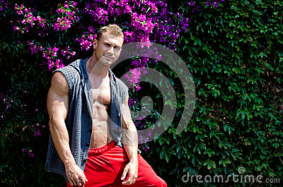 Handsome muscular young man outdoors with flowers behind