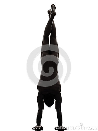 Handsome naked muscular man exercising handstand  silhouette