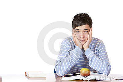 Handsome sad male student learns with study books