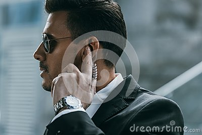 handsome security guard standing and listening message with security Stock Photo