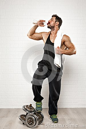Free Handsome Sportsman Standing With Towel Holding A Bottle Of Water While Drinking Over White Background. Royalty Free Stock Image - 113168166