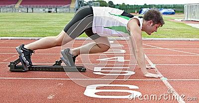Handsome sprinter on the starting line in stadium
