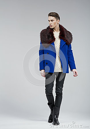 Handsome young man dressed in blue coat