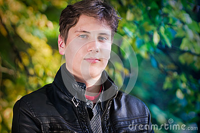 Handsome teen portrait in autumn leaves background