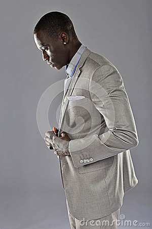 Black man in a suit adjust his coat