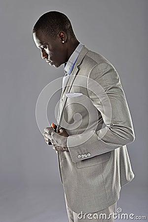 Black man in a suit adjust his coat