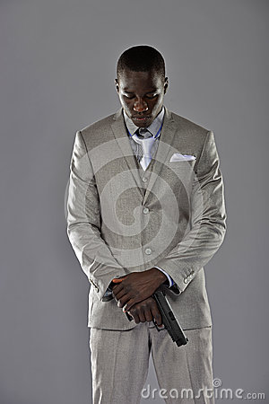 Man in a suit looks down as he holds his gun