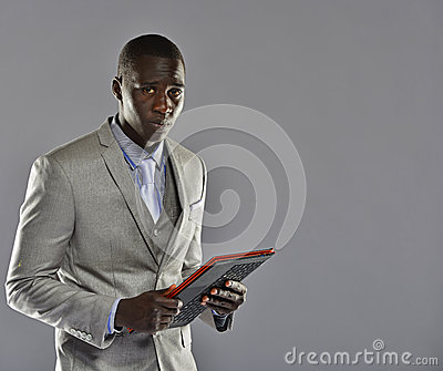 Black man in a suit holding tablet computer