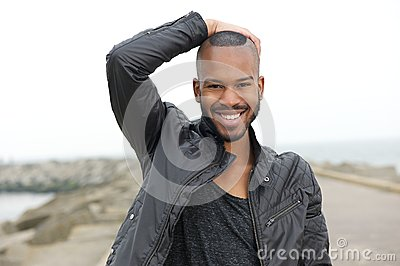 Handsome young black man smiling outdoors