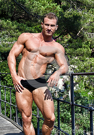 Handsome young bodybuilder shirtless outdoors in sunny day