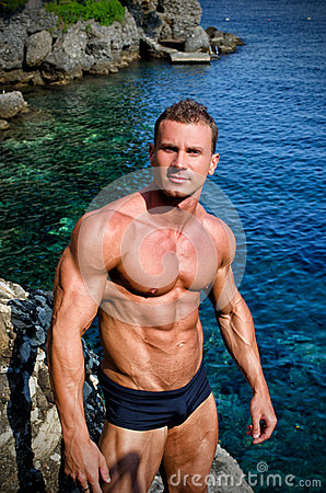 Handsome young bodybuilder shirtless by the sea or ocean
