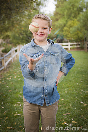 Handsome Young Boy Tossing Up Baseball in the Park Stock Photo