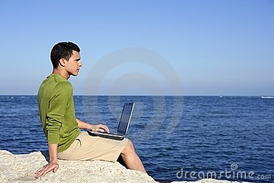 Handsome young businessman computer beach