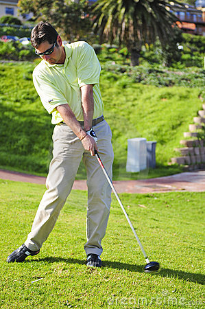 Handsome young golfer in action