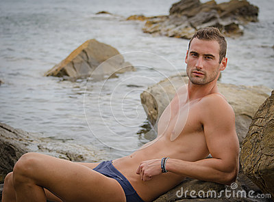 Handsome young man in bathing suit sitting
